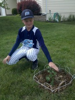 Owen posing next to a tiny tree we planted last year in our front yard.